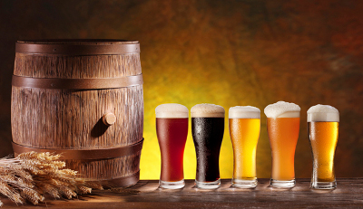 Assortment of beer glasses with a wooden barrel.
